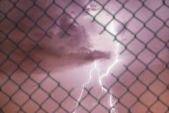 Imagem conceptual do relâmpago no céu tormentoso e na cerca de fio de aço da malha foto de stock