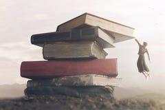 Imagem conceptual uma mulher corajoso que escala uma pilha dos livros para alcançar a parte superior imagens de stock royalty free