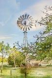 Imagem convertida Painterly de um moinho de vento australiano que bombearam com sucesso a água no interior australiano em calhas  imagem de stock