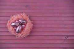 Imagem cor-de-rosa do tempo da Páscoa da cor com os ovos da páscoa envolvidos brilhantes do chocolate em um ninho com espaço imagens de stock royalty free