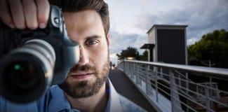 Imagem 3d composta do retrato do fotógrafo masculino que fotografa através da câmera Fotografia de Stock