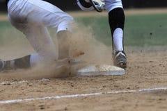 Imagem da ação do basebol - os pés primeiramente deslizam na base Fotos de Stock