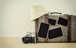 Imagem da bagagem velha do vintage, do chapéu do fedora, da câmera velha da foto do vintage e de fotos vazias para o modelo da mo Foto de Stock Royalty Free
