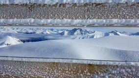 Imagem da cerca congelada com as montanhas cobertos de neve bonitas no fundo imagem de stock