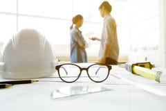 A imagem da engenharia objeta no local de trabalho com três sócios dentro Imagens de Stock Royalty Free