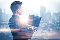 A imagem da exposição dobro do homem de negócio que usa um laptop durante o nascer do sol overlay com imagem da arquitetura da ci fotografia de stock royalty free