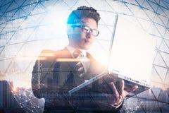 A imagem da exposição dobro do homem de negócios que usa um laptop durante o nascer do sol overlay com imagem da arquitetura da c foto de stock