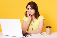 A imagem da fêmea atrativa nova que olha o laptop e que olha o filme de terror, receosa de algo, morde seus pregos, completamente foto de stock