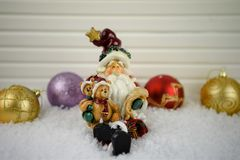 Imagem da fotografia do Natal do ornamento de Santa Claus que senta-se na neve com vermelho e nas decorações da árvore do brilho  Foto de Stock Royalty Free