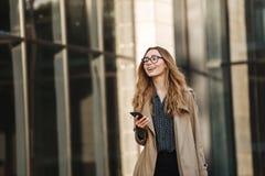 Imagem da jovem mulher que usa o telefone celular ao andar através da rua da cidade fotografia de stock royalty free