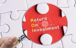 Imagem da lupa que centra-se sobre o retorno sobre o investimento Imagens de Stock