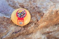 Imagem da máquina de Gumball pintada na rocha amarela pequena Imagem de Stock