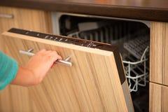 Imagem da mão da máquina de lavar louça da abertura do homem fotos de stock royalty free