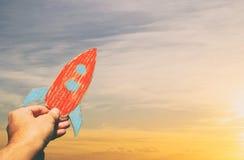 Imagem da mão masculina que mantém um foguete contra o céu imaginação e conceito do sucesso foto de stock