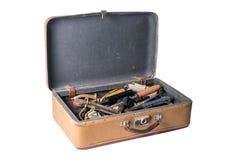 Imagem da mala de viagem retro aberta completamente das ferramentas de funcionamento velhas isoladas imagens de stock