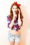 Imagem da menina bonita da jovem mulher do pinup com o batom vermelho que olha a câmera no telefone celular móvel Fotos de Stock Royalty Free