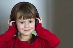 Imagem da menina bonita feliz da criança com fones de ouvido grandes em casa A menina alegre da criança que escuta a música no ci imagem de stock