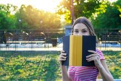 Imagem da menina bonita nova que esconde atrás do livro no parque do verão imagem de stock