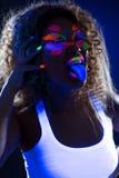 Imagem da menina engraçada que levanta na câmera na luz UV Foto de Stock