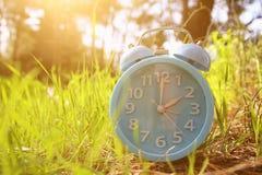Imagem da mudança do tempo de mola Conceito traseiro do verão Despertador do vintage fora fotografia de stock royalty free