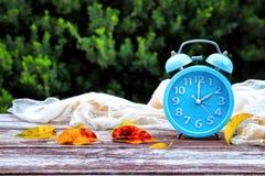 Imagem da mudança do tempo do outono Recuar o conceito Seque as folhas e o despertador do vintage na tabela de madeira Imagem de Stock