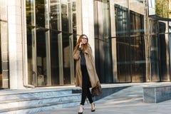 Imagem da mulher alegre que usa o telefone celular ao andar através da rua da cidade fotos de stock