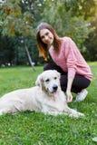 Imagem da mulher com o cão que encontra-se no gramado no parque do verão fotografia de stock royalty free