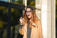 Imagem da mulher entusiasmado que usa o telefone celular ao andar através da rua da cidade imagens de stock