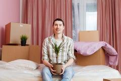 Imagem da mulher feliz que senta-se no sofá entre caixas de cartão foto de stock