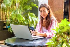 Imagem da mulher feliz que usa o portátil e o smartphone no café fotos de stock royalty free
