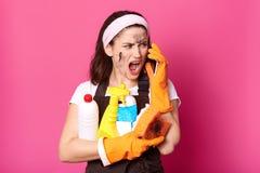 A imagem da mulher gritando que fala no telefone celular ao limpar em casa, vestiu a camisa de t, o avental e o hairband, senhora imagem de stock royalty free