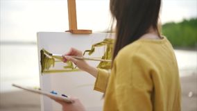 Imagem da paisagem da aquarela do desenho do pintor da jovem mulher na armação video estoque