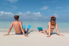Imagem da parte traseira de um par novo com aletas e da máscara assentada em uma praia branca em Maldivas ?gua azul claro como imagens de stock royalty free