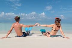 Imagem da parte traseira de um par novo com aletas e da m?scara assentada em uma praia branca em Maldivas ?gua azul claro como fotografia de stock