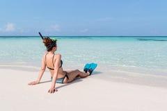 Imagem da parte traseira de uma jovem mulher com aletas e da máscara assentada em uma praia branca em Maldivas Água azul claro co fotografia de stock