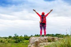 A imagem da parte traseira do turista fêmea com braços aumentou no monte imagem de stock royalty free