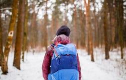 Imagem da parte traseira da mulher de passeio com a trouxa sobre a floresta do inverno imagem de stock royalty free
