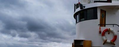Imagem da ponte de um barco de pesca entrado em um porto em Islândia em um dia nebuloso fotos de stock royalty free