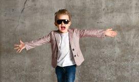 Imagem da posição entusiasmado alegre da criança do rapaz pequeno isolada sobre o muro de cimento imagem de stock royalty free