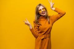 Imagem da posição feliz da jovem mulher isolada sobre o fundo amarelo que mostra o gesto da paz olhando a câmera fotos de stock royalty free