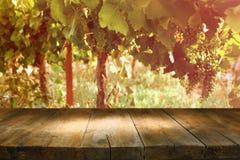 Imagem da tabela de madeira na frente da paisagem do vinhedo Foto de Stock
