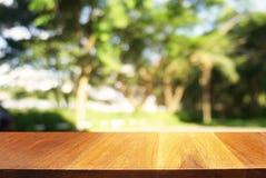a imagem da tabela de madeira na frente do sumário borrou o fundo de Imagens de Stock
