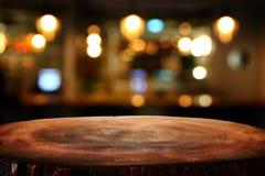A imagem da tabela de madeira na frente do sumário borrou o fundo das luzes do restaurante fotografia de stock royalty free