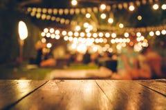 A imagem da tabela de madeira na frente do sumário borrou o fundo das luzes do restaurante imagens de stock