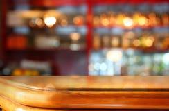 A imagem da tabela de madeira na frente do sumário borrou o fundo de luzes do restaurante Fotografia de Stock Royalty Free