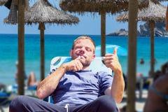 Imagem da vida da praia com borrão desejado Foco no homem na cadeira de plataforma Fotos de Stock