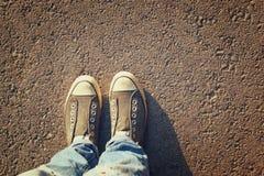 Imagem da vista superior da pessoa com as sapatas sobre a estrada asfaltada Imagens de Stock