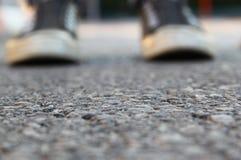 Imagem da vista superior da pessoa com as sapatas sobre a estrada asfaltada Imagens de Stock Royalty Free