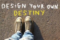 Imagem da vista superior da pessoa nas calças de brim e sapatilhas com o texto - projete seu próprio destino Imagem de Stock Royalty Free
