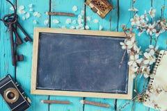 Imagem da vista superior da árvore branca das flores de cerejeira da mola, quadro-negro, câmera velha na tabela de madeira azul Foto de Stock